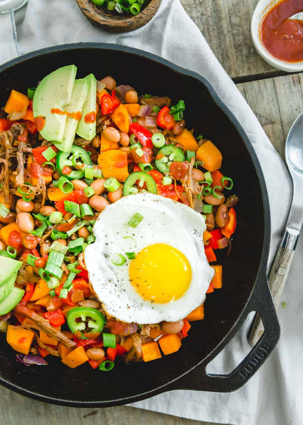 This easy skillet brisket hash recipe includes beans, sweet potatoes, peppers and a fried egg on top.