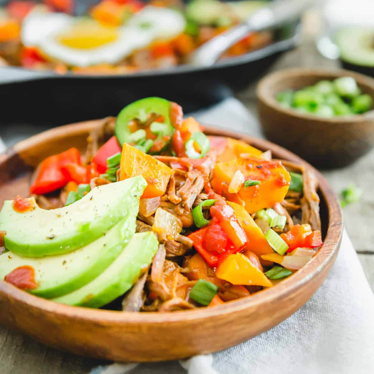 Brisket breakfast hash with sweet potatoes, peppers, beans and sliced avocado for serving.