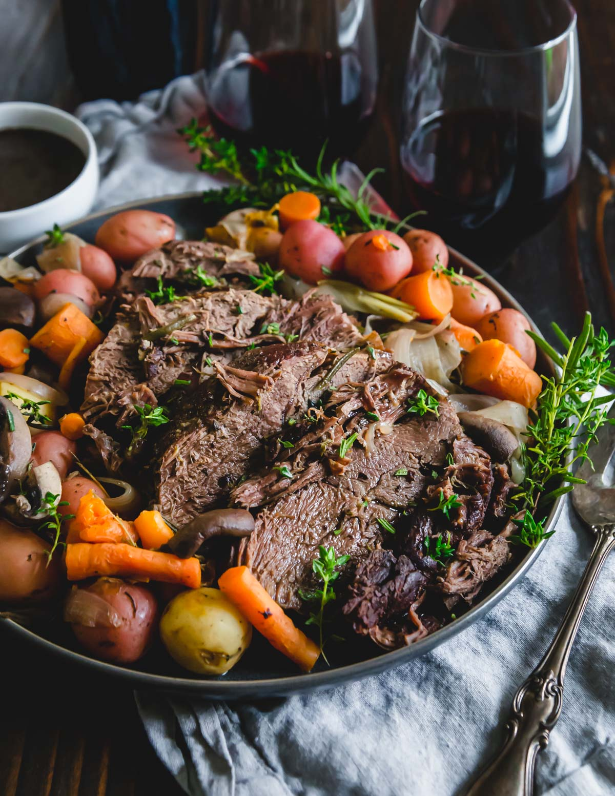 tender pressure cooked venison roast with potatoes, carrots, mushrooms and onions