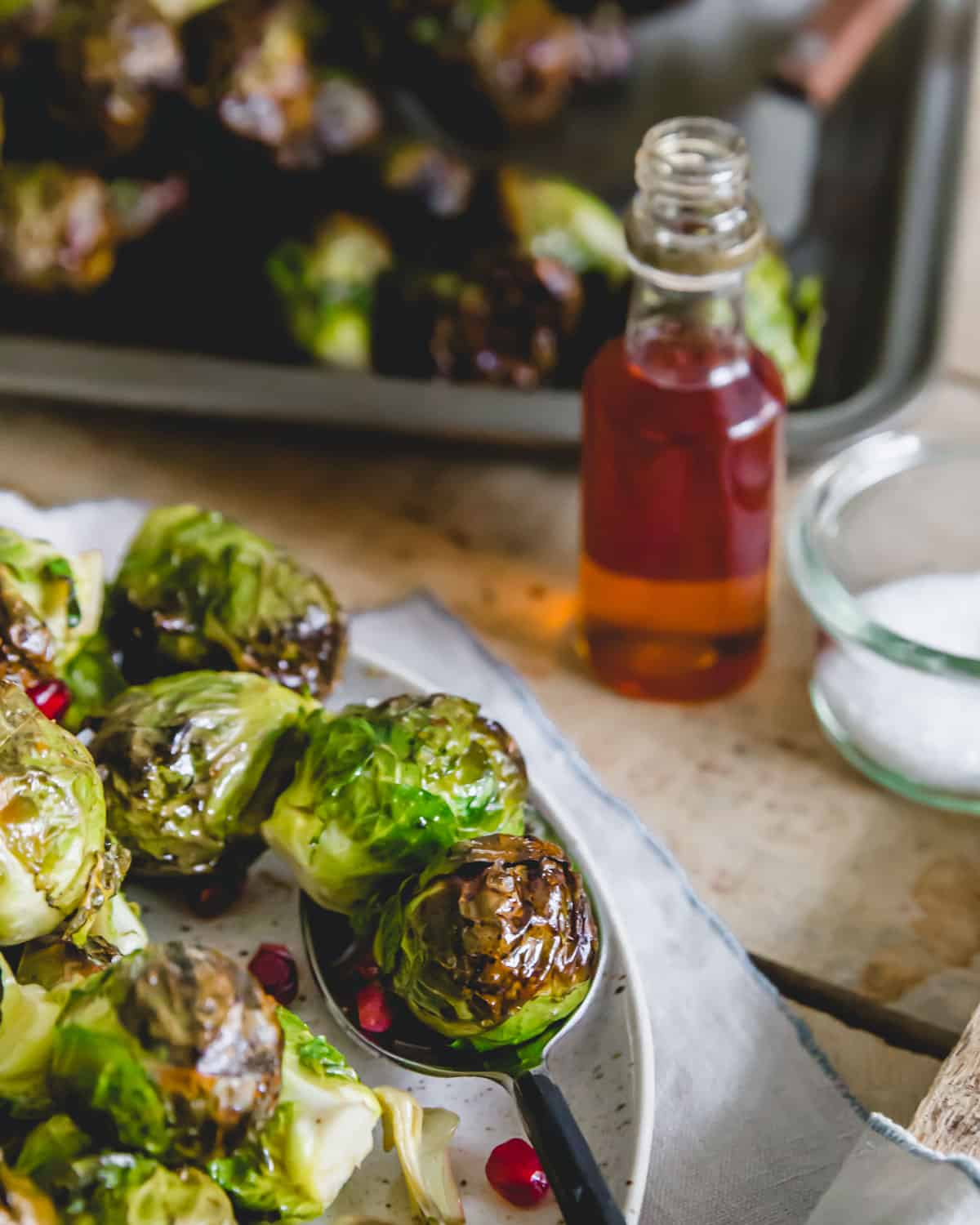 Tender maple roasted on the stalk Brussels sprouts plated and served with fresh pomegranate arils.