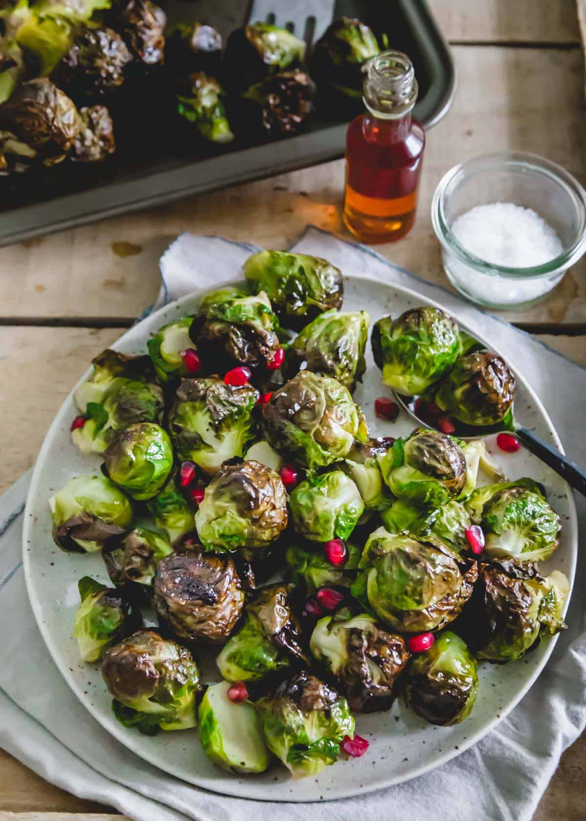 Brussels sprouts roasted on the stalk then cut off and plated with maple balsamic glaze.