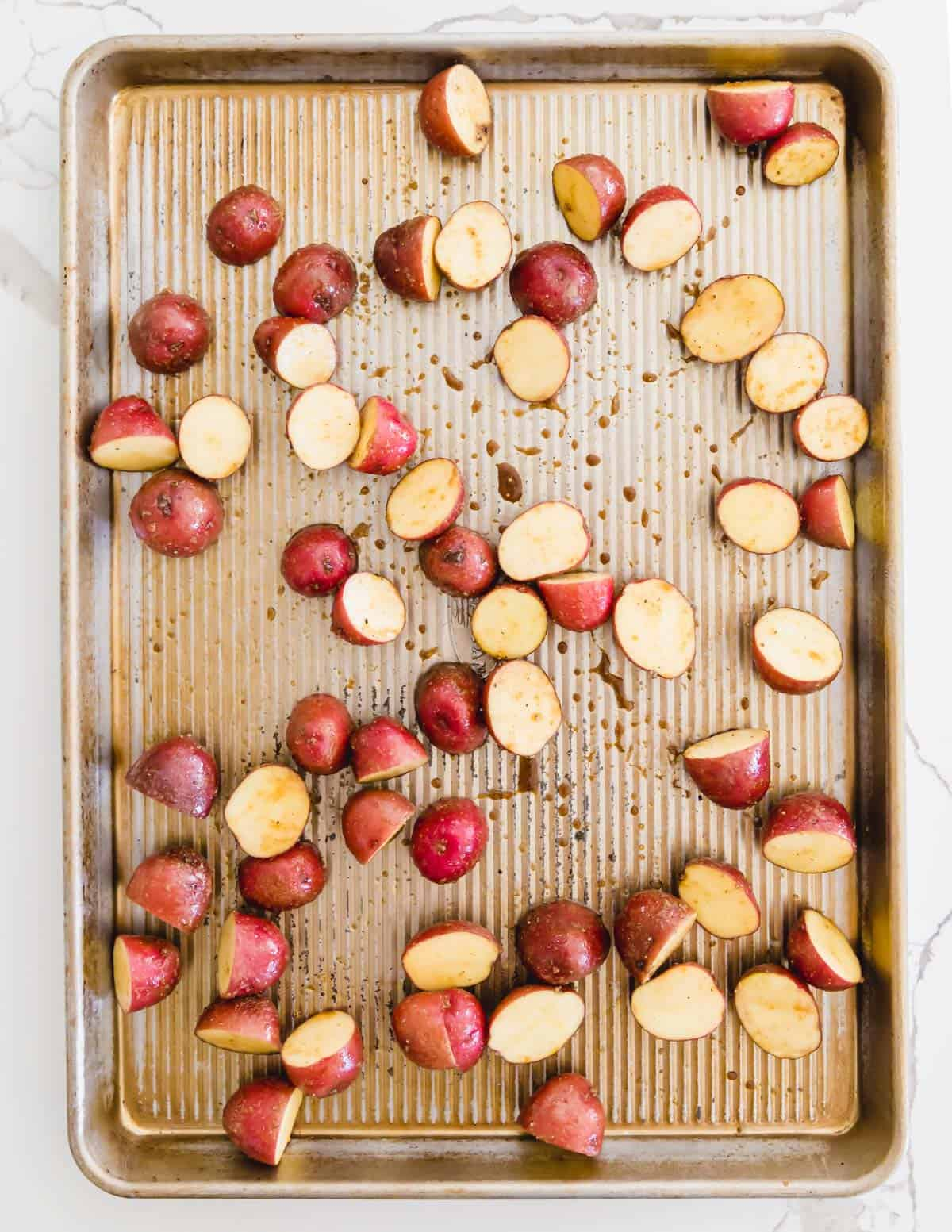 baby red potatoes on a sheet pan to roast with asparagus