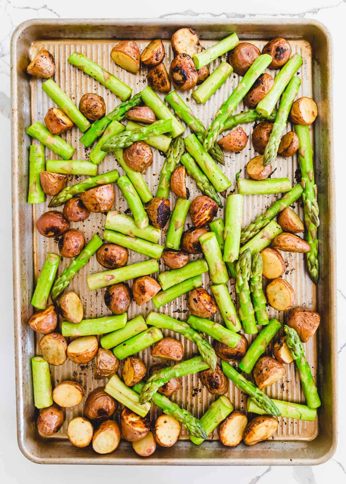 roasted red potatoes with fresh asparagus spears on a baking sheet