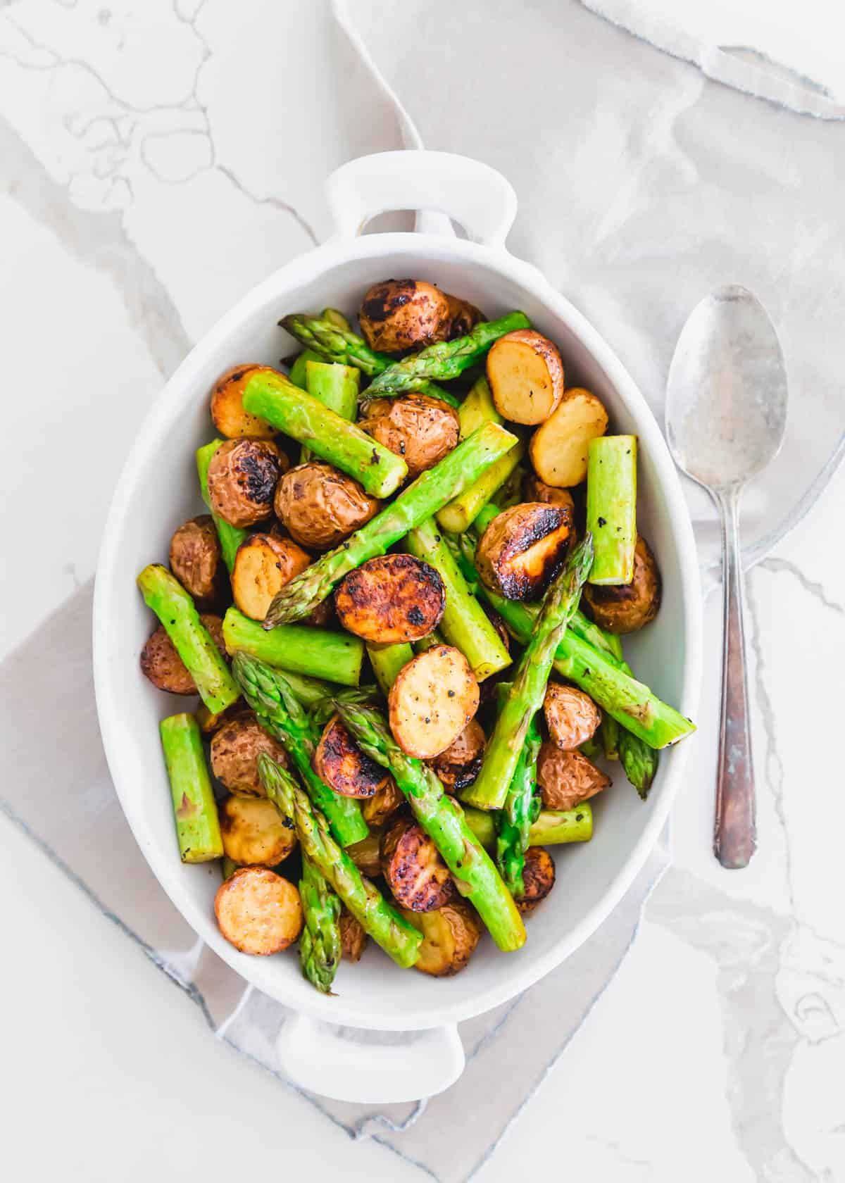 This easy side dish of oven roasted potatoes and asparagus is made all on one baking sheet with garlic balsamic seasoning.