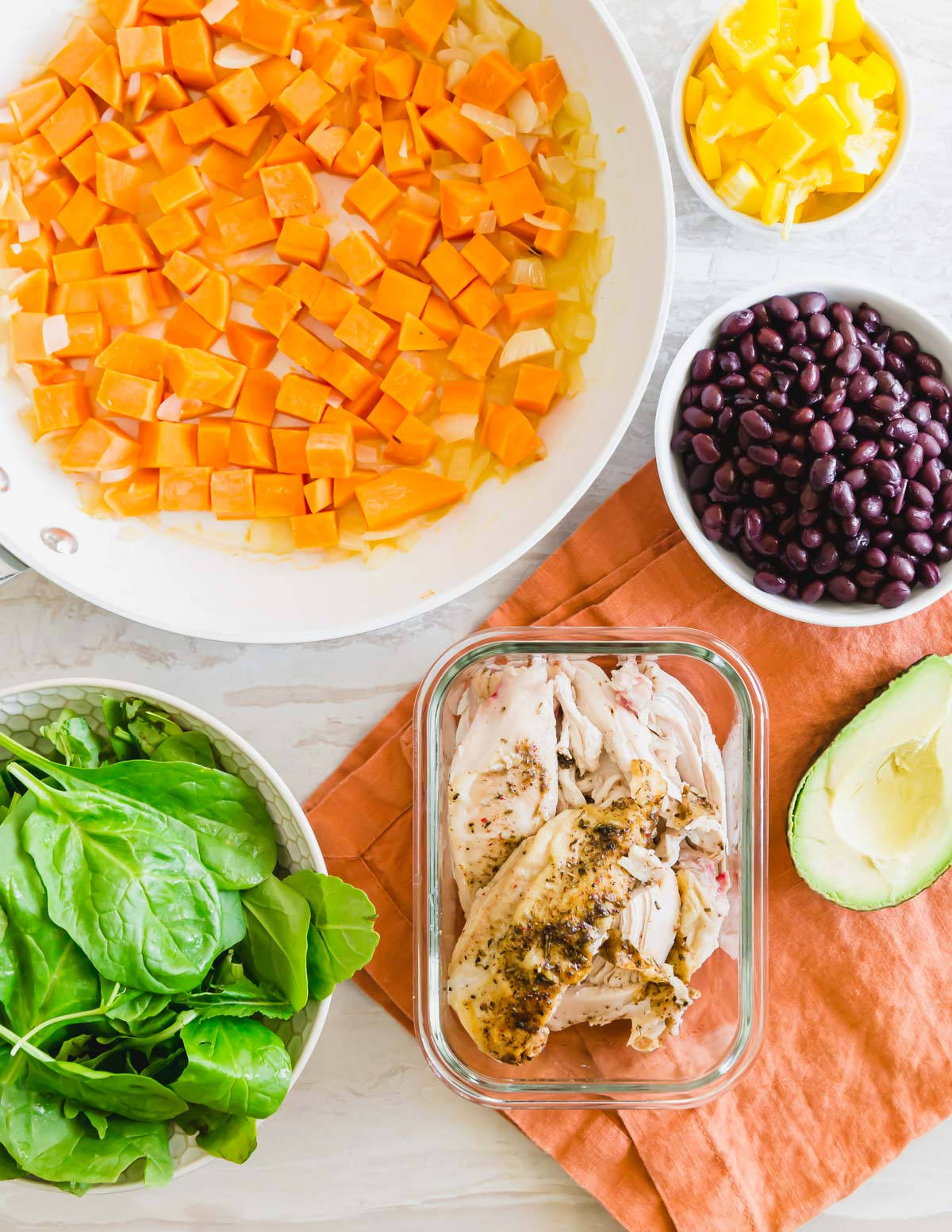 ingredients for this one pan turkey sweet potato skillet including sweet potatoes, onions, yellow bell pepper, black beans, baby greens and leftover turkey.