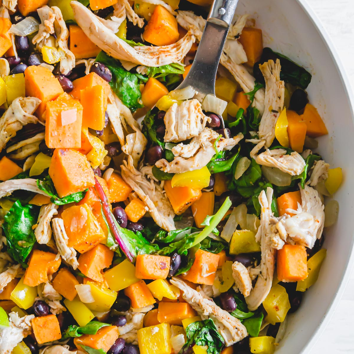 An easy meal perfect for using up leftover turkey from Thanksgiving with sweet potatoes, black beans, peppers, onions and baby greens.