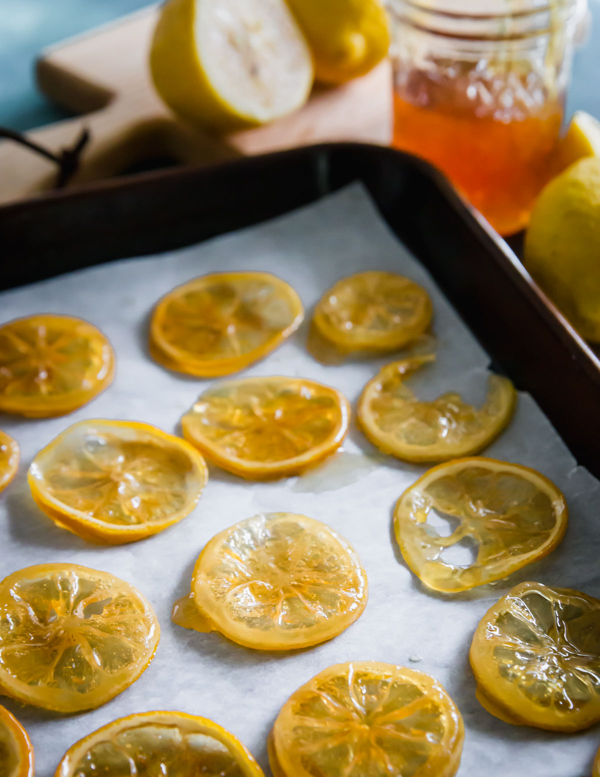 Candied lemon slices drying on a sheet pan