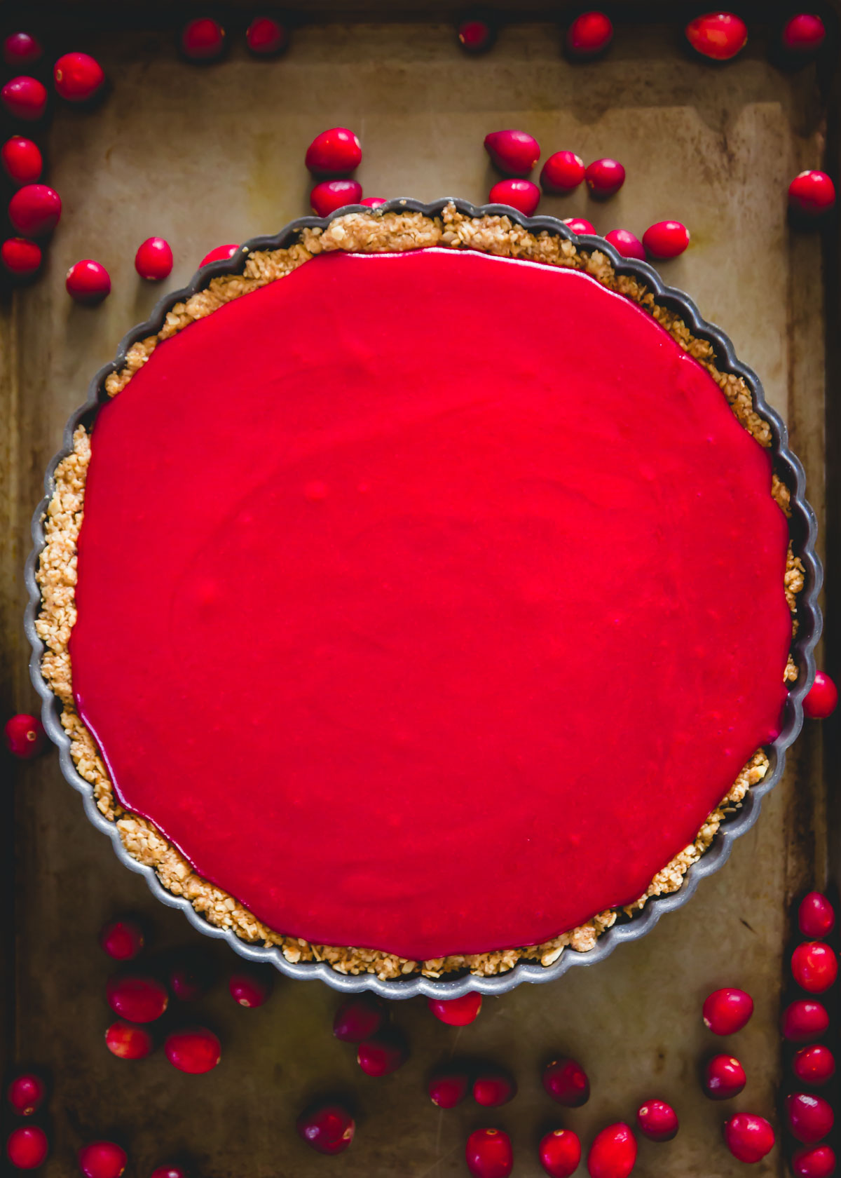 Easy cranberry curd tart with oat and walnut tart crust before setting.