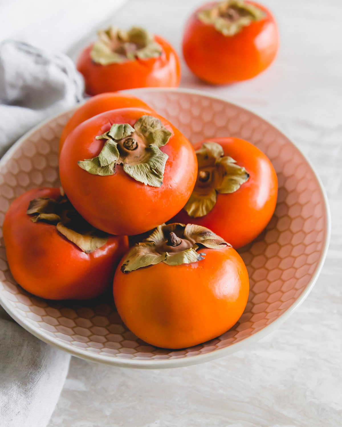 Fuyu persimmons in a bowl to make persimmon jam