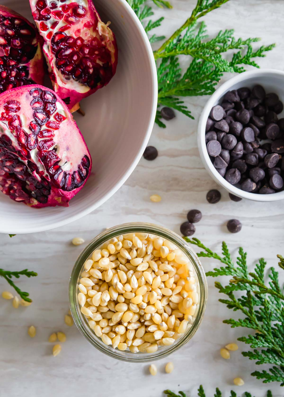 Ingredients to make pomegranate popcorn include popping corn kernels, pomegranate arils and dark chocolate chips.