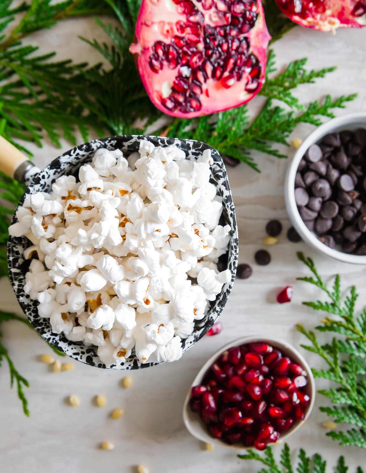 Freshly popped corn in coconut oil is tossed with bright and festive pomegranate, dark chocolate chips and a dusting of lemon zest.