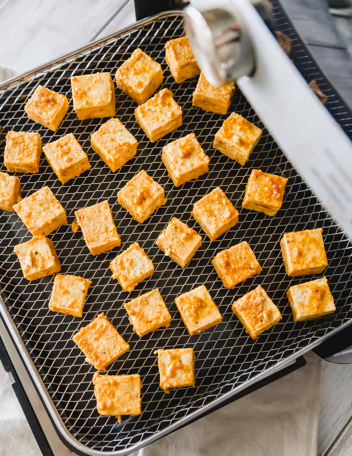 Cubed tofu with tamari, olive oil, garlic and onion powder on a Pampered Chef air fryer tray.