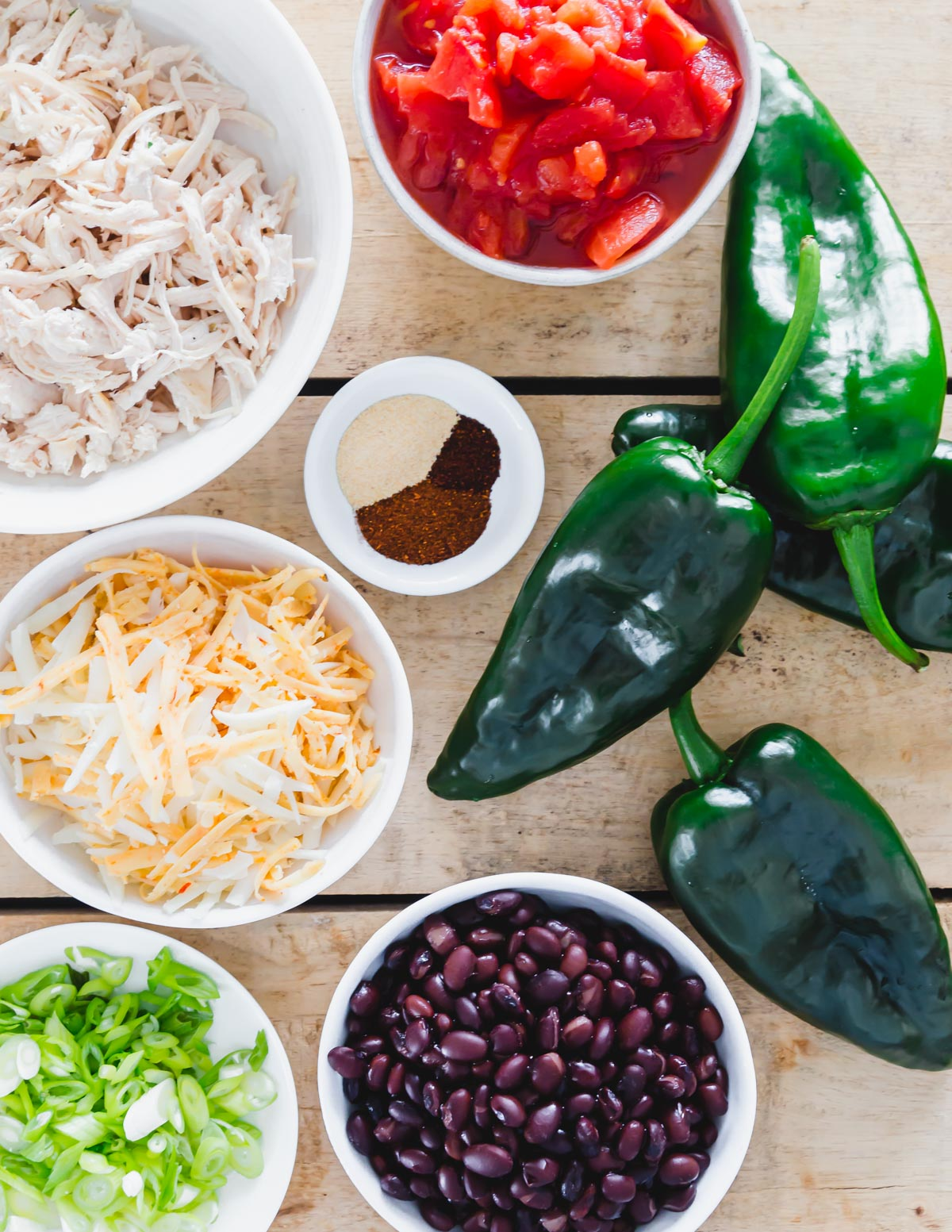 Ingredients to make stuffed poblano peppers including shredded cooked chicken, cheese, black beans, tomatoes and spices.