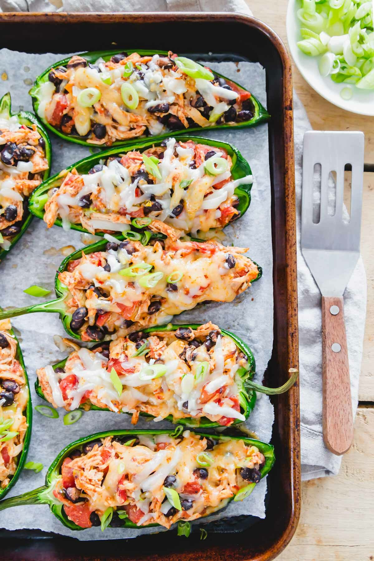 Spicy stuffed Mexican poblano peppers with chicken, black beans, tomatoes and lots of melted cheese are an easy weeknight meal everyone will love!