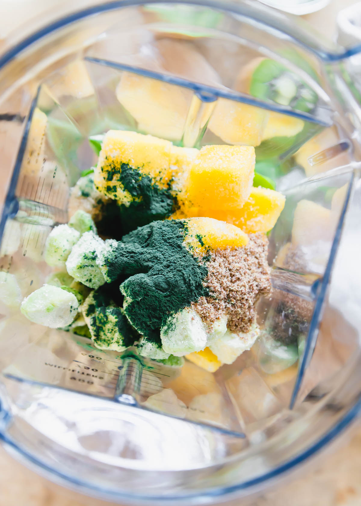 spirulina, mango, banana, kiwi, baby greens and flax seeds in the blender to make a smoothie