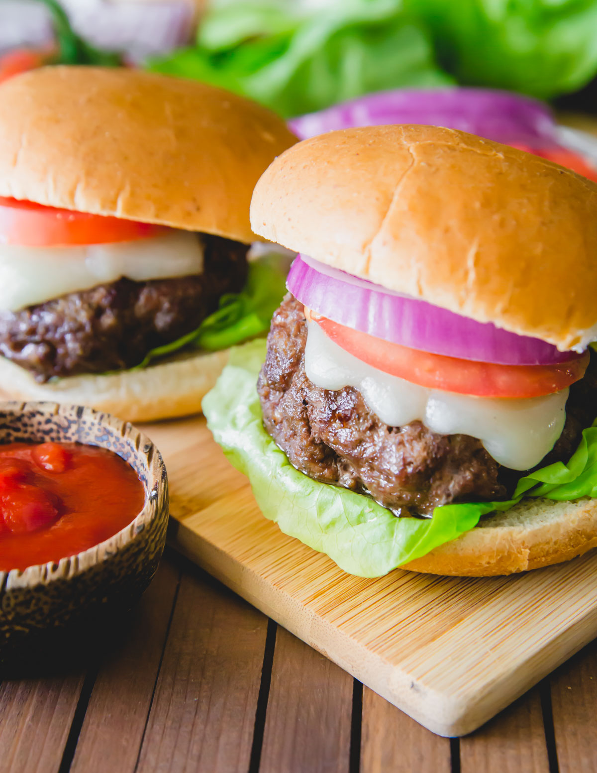 Elk burger made with ground elk meat, ghee and spices on a bun with melted cheese, lettuce, tomato and onion.