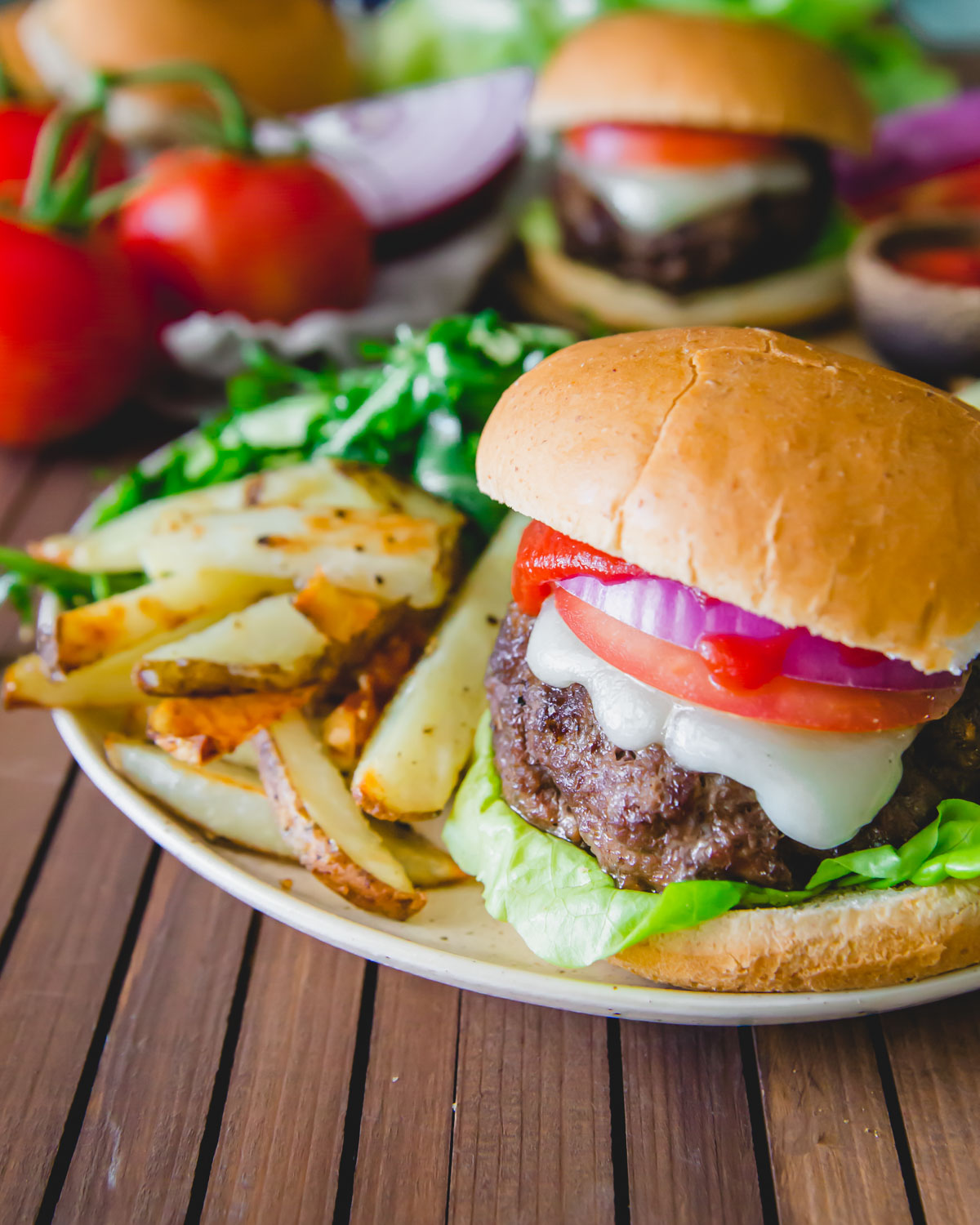 Perfectly grilled and juicy elk burger on a bun with melted cheddar, lettuce, tomato, red onion and ketchup. Served with fries and a salad.