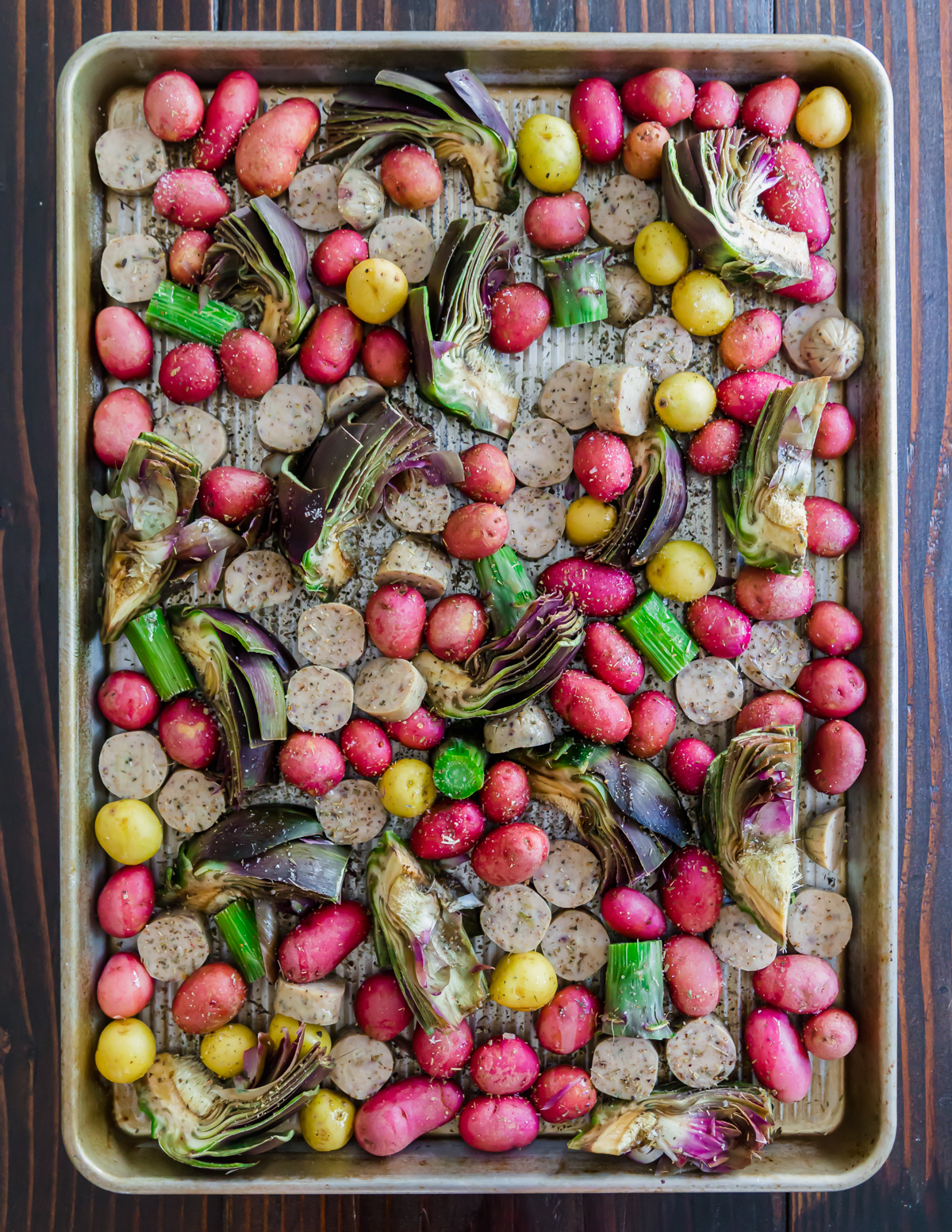 Sliced sausage links, baby potatoes and purple artichokes are added to a baking sheet for this easy dinner recipe.