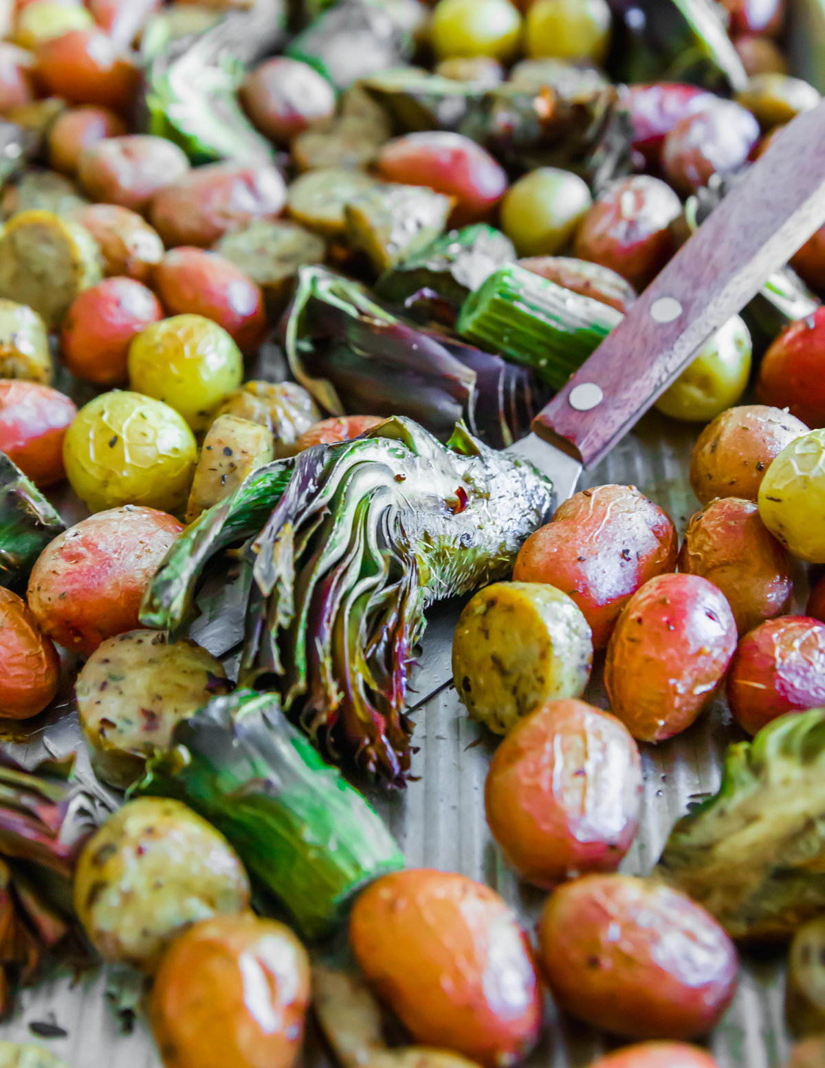 The trimmed purple artichokes roast until tender with the baby potatoes and sausage in this easy sheet pan meal.
