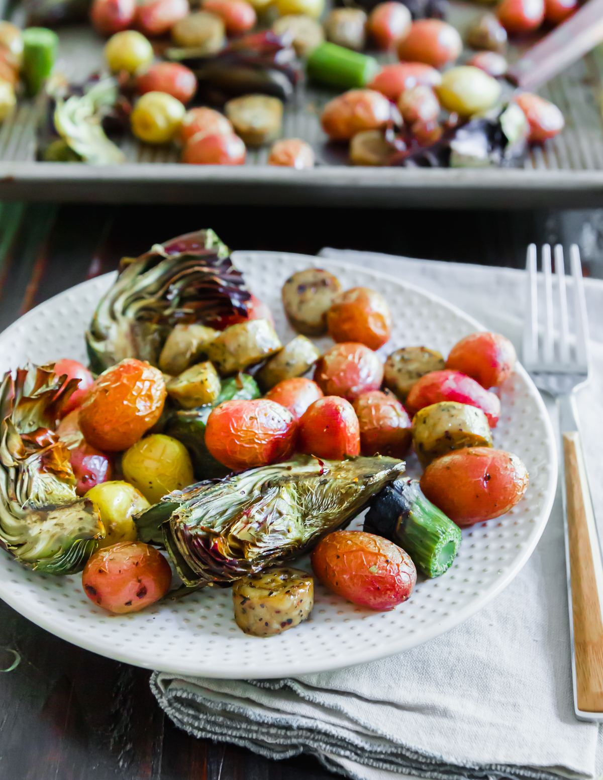 Sheet pan sausage and vegetables is a complete meal with tender purple roasted artichokes, baby potatoes and sliced chicken sausage.