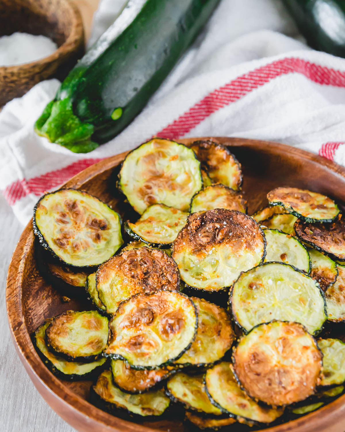 Crispy air fried zucchini chips on a plate seasoned with garlic powder.
