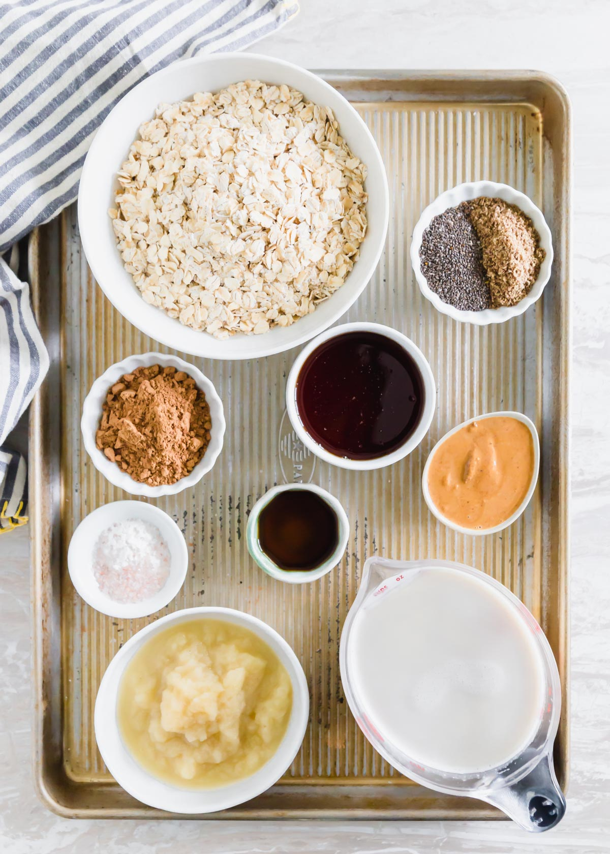 Ingredients to make baked chocolate oats including, rolled oats, chia and flax seeds, maple syrup, cacao powder, almond butter, vanilla, baking powder, salt, applesauce and milk of choice.