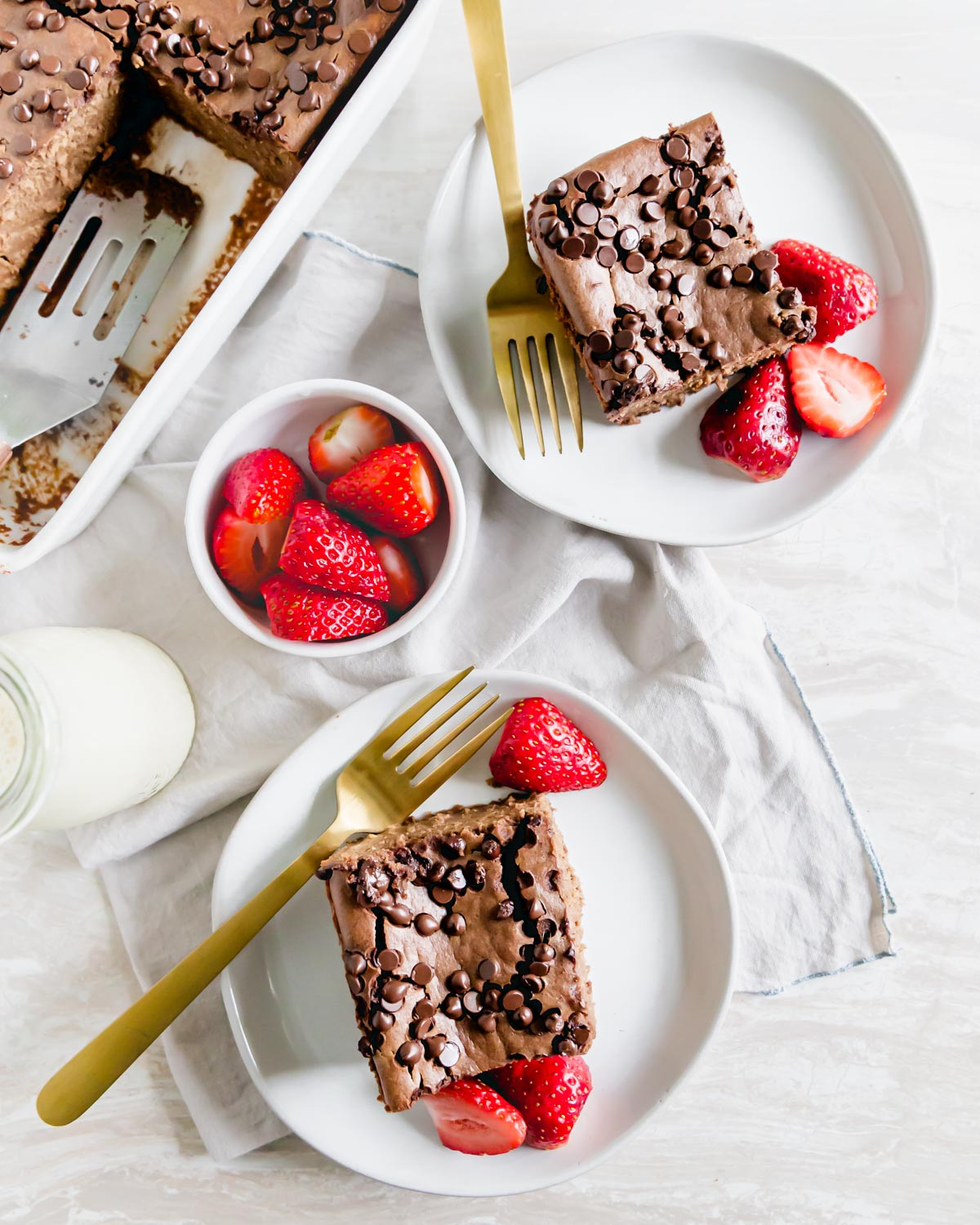 Two slices of baked chocolate oats on plates garnished with fresh strawberries for serving.