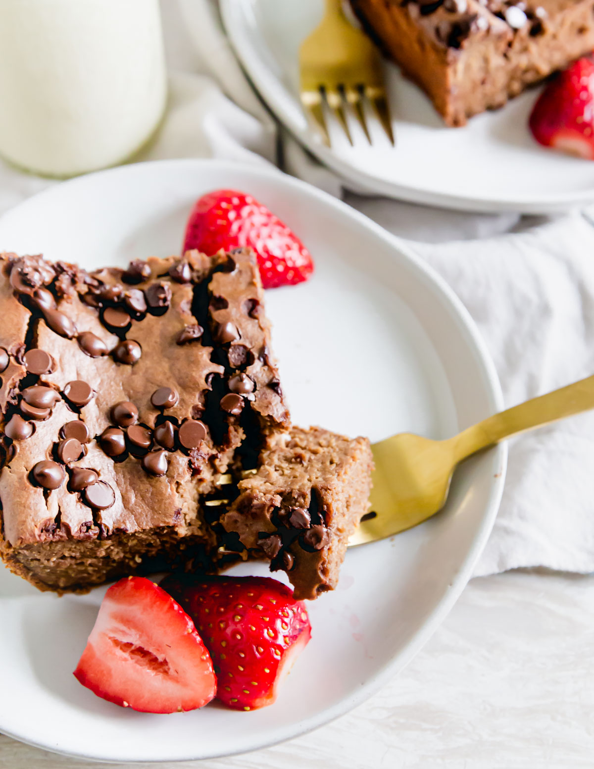 A slice of chocolate baked oats on a plate with a piece on the fork. Fresh strawberries in the background.