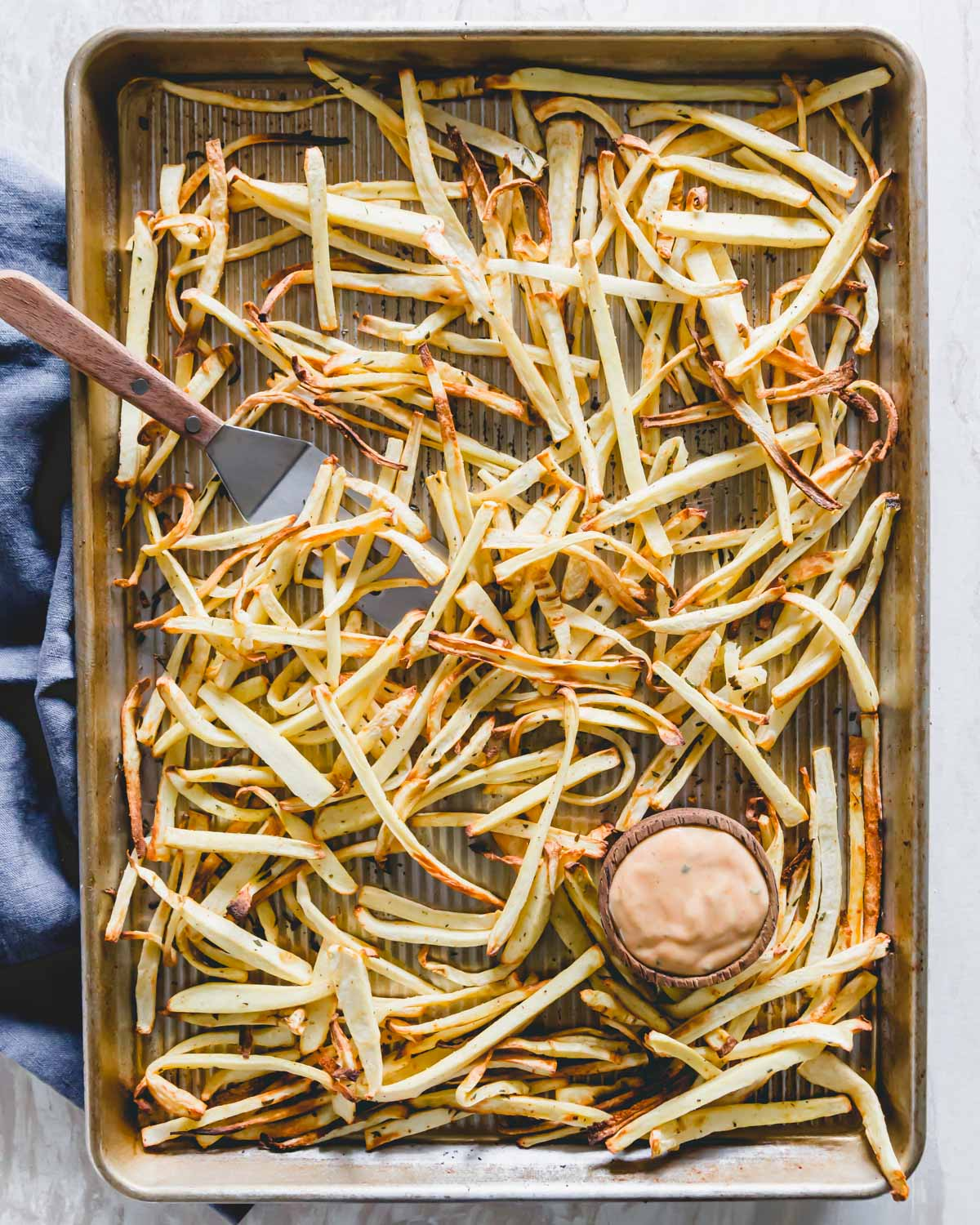 Crispy baked parsnip fries on a baking sheet with a fry sauce for dipping.