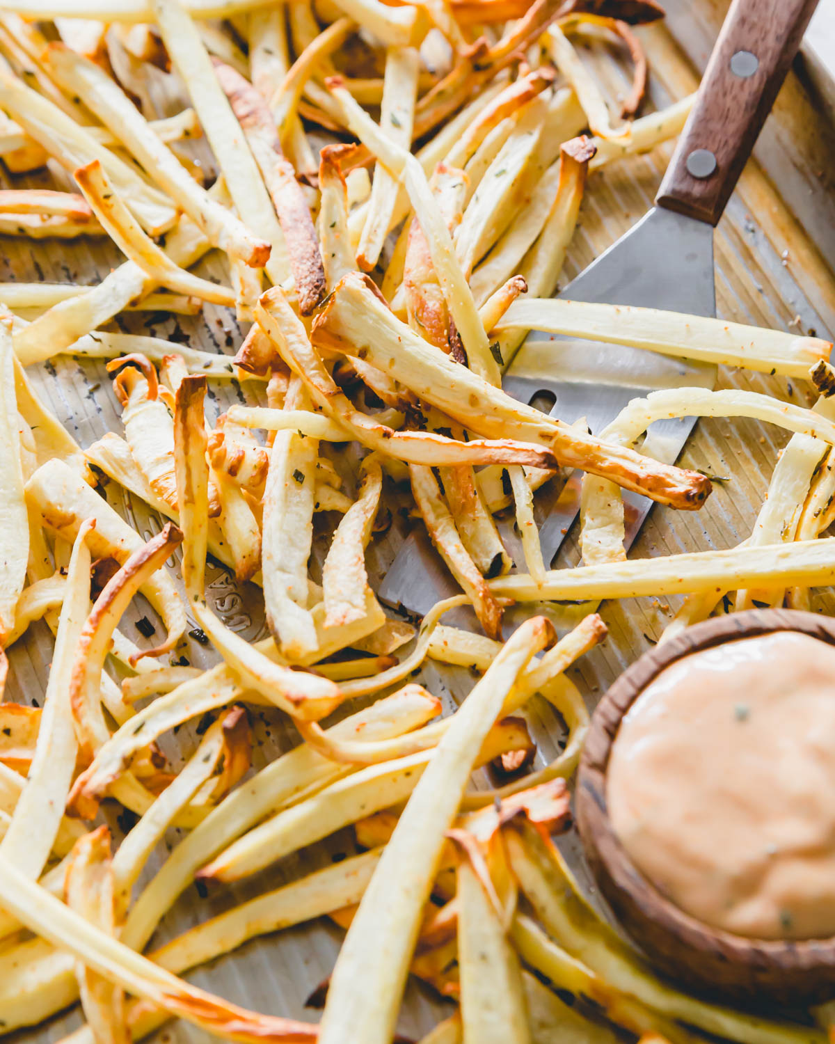 Crispy golden brown parsnip fries straight out of the air fryer and oven on a baking sheet with fry sauce and a spatula for serving.