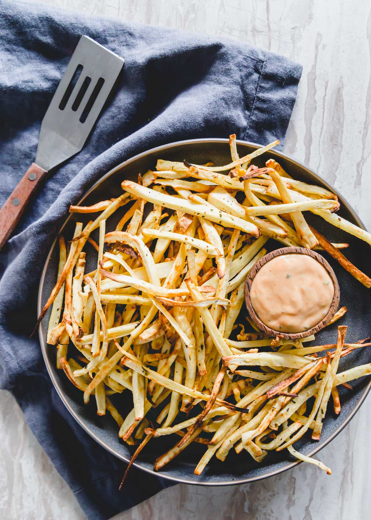 Rosemary garlic baked parsnip fries with a ketchup and mayonnaise dipping sauce on a serving plate.
