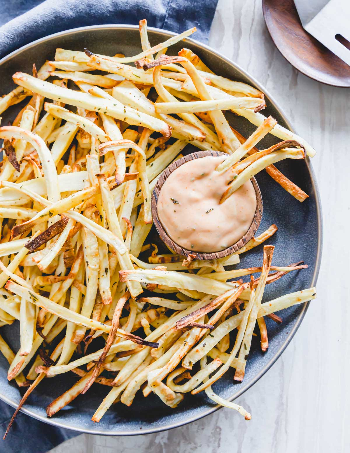Crispy parsnip fries with rosemary and garlic seasoning served on a plate with an easy fry-sauce.