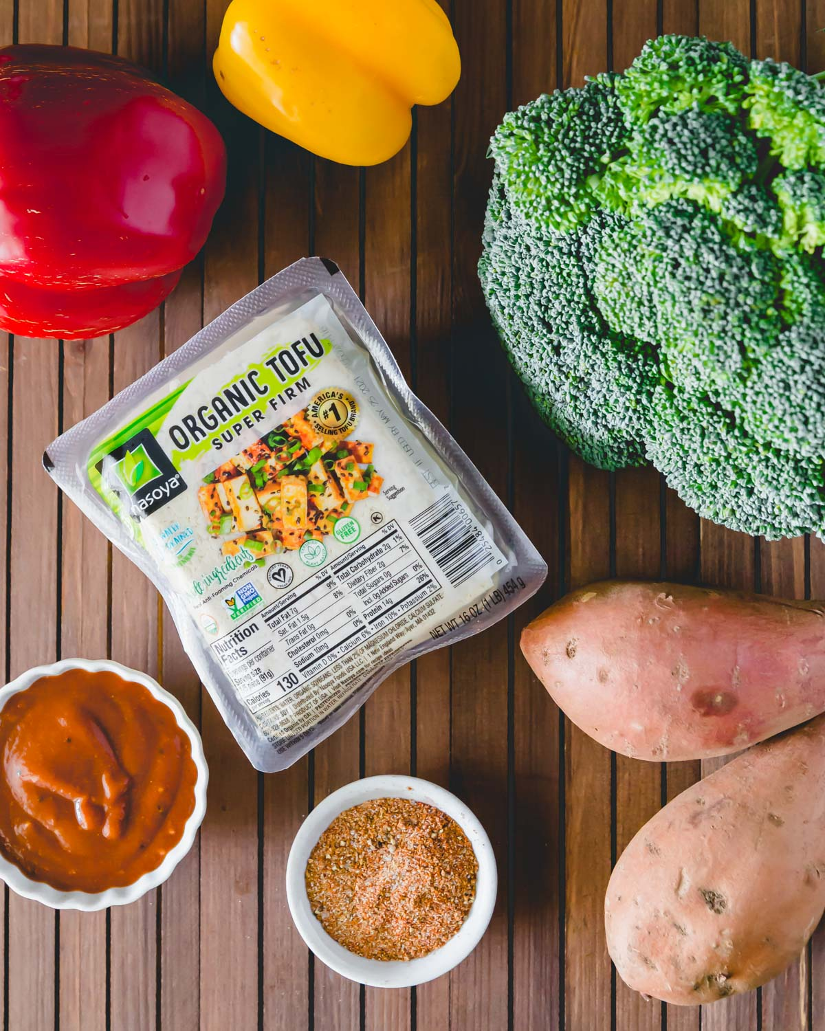 Ingredients to make sheet pan BBQ tofu in the oven: BBQ sauce, organic tofu, broccoli, sweet potato, bell peppers and a dry spice rub.