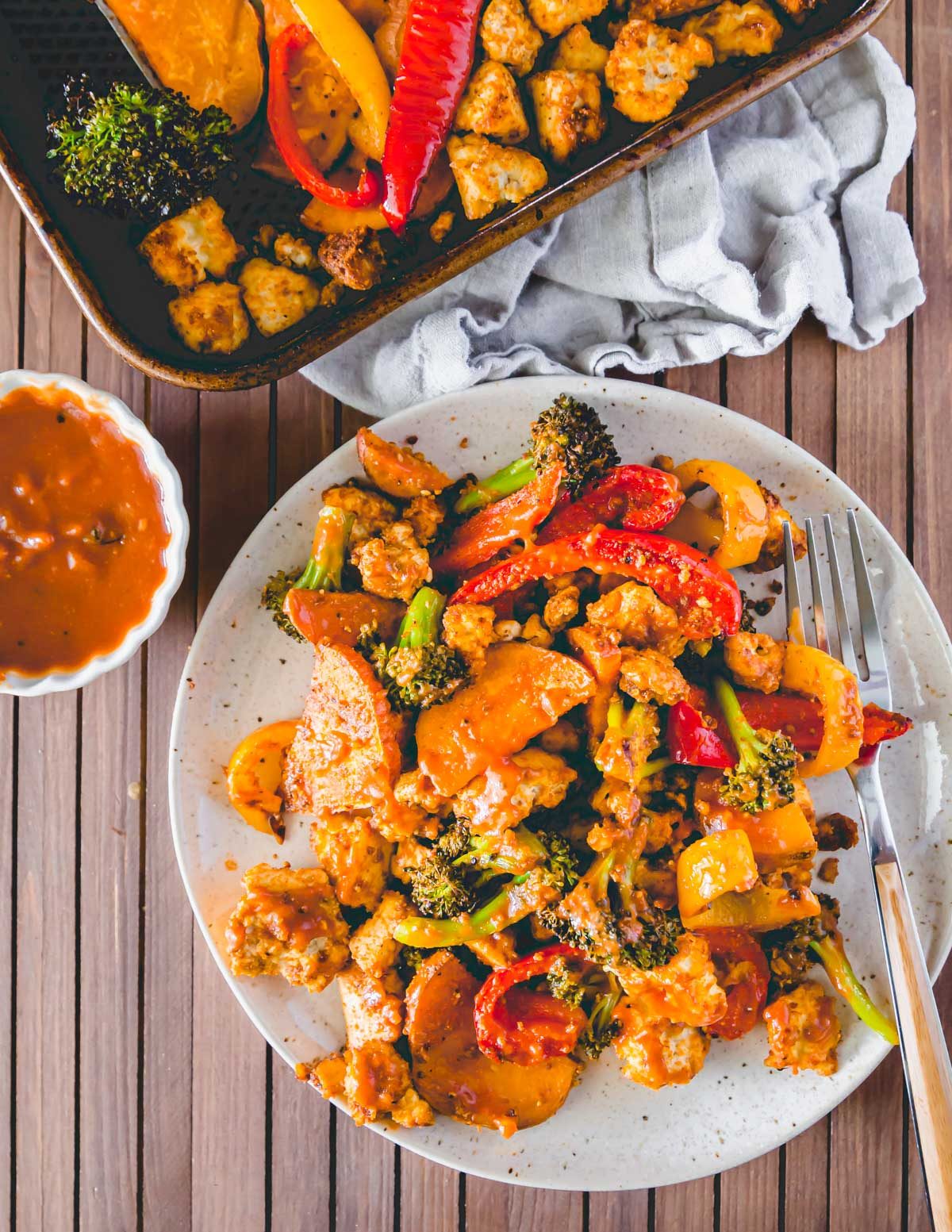 BBQ tofu, broccoli, peppers and sweet potatoes made on a baking sheet in the oven.