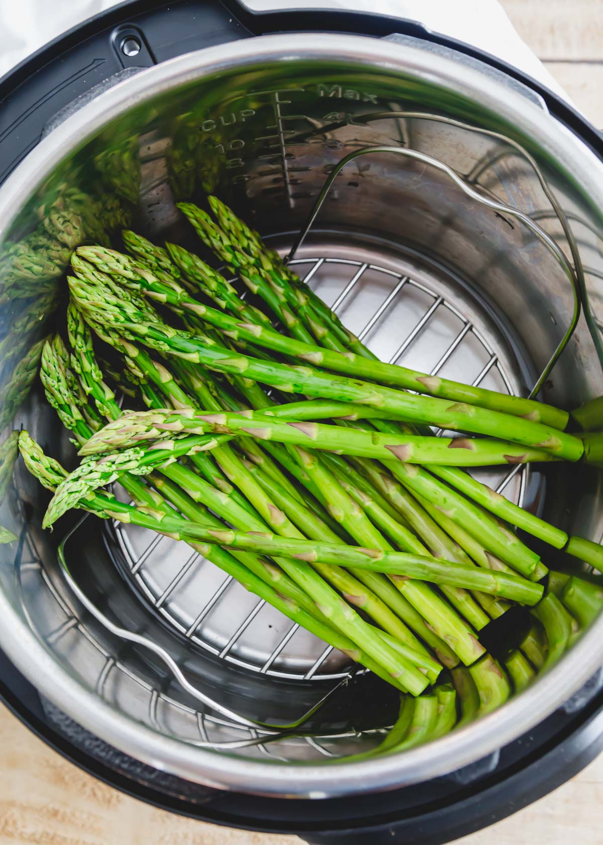 Raw asparagus spears inside an Instant Pot atop the metal trivet.