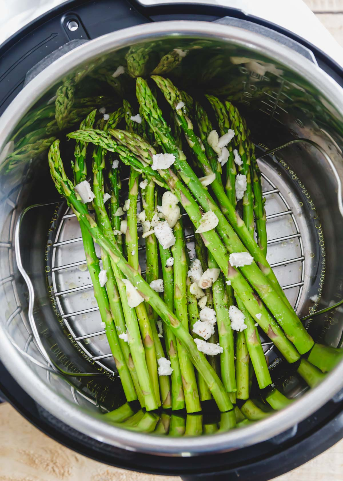 Raw asparagus spears in an Instant Pot with olive oil, butter and garlic on top and water on the bottom of the insert.
