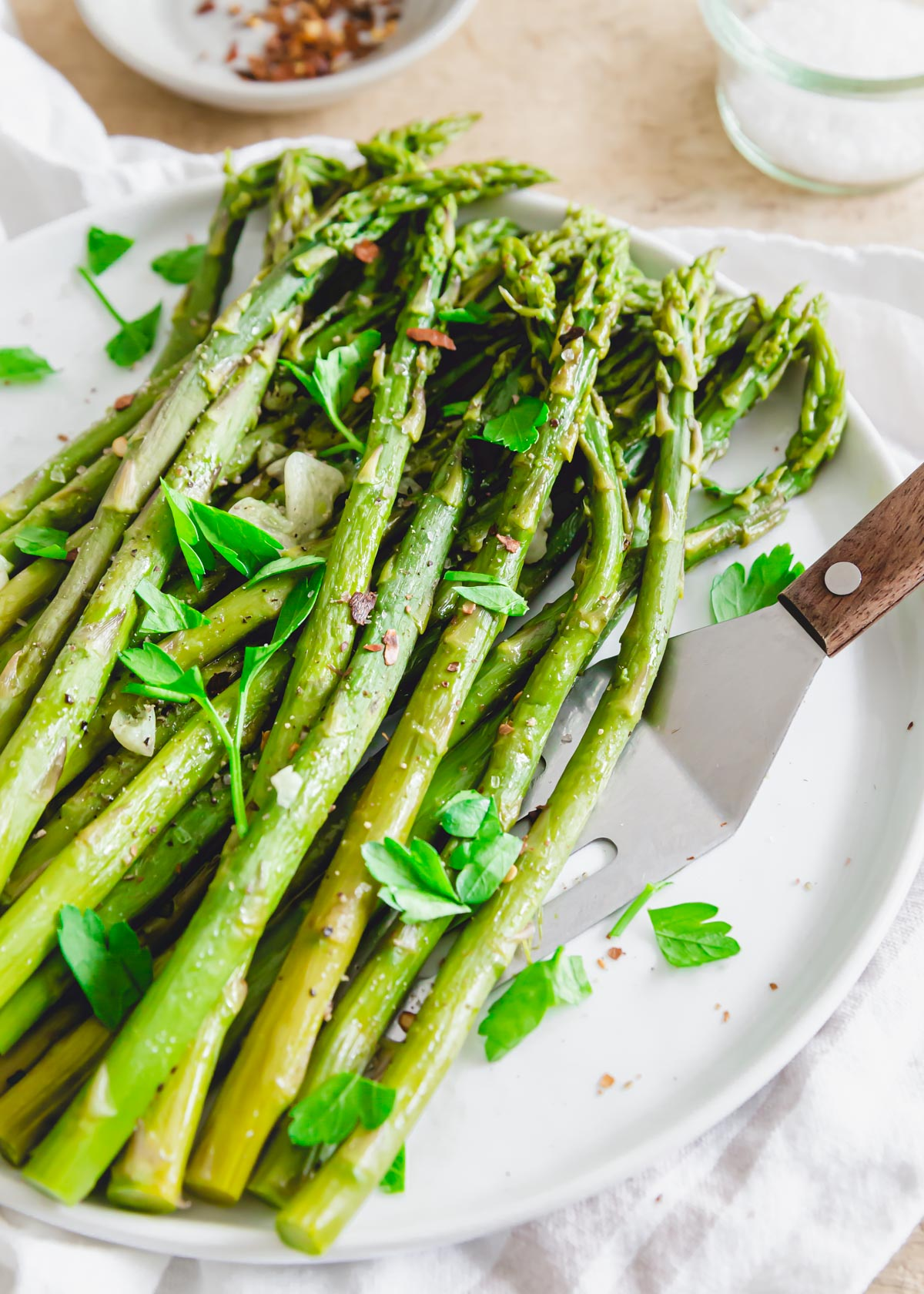 Asparagus cooked in the Instant Pot in just minutes on a plate with a serving spatula.