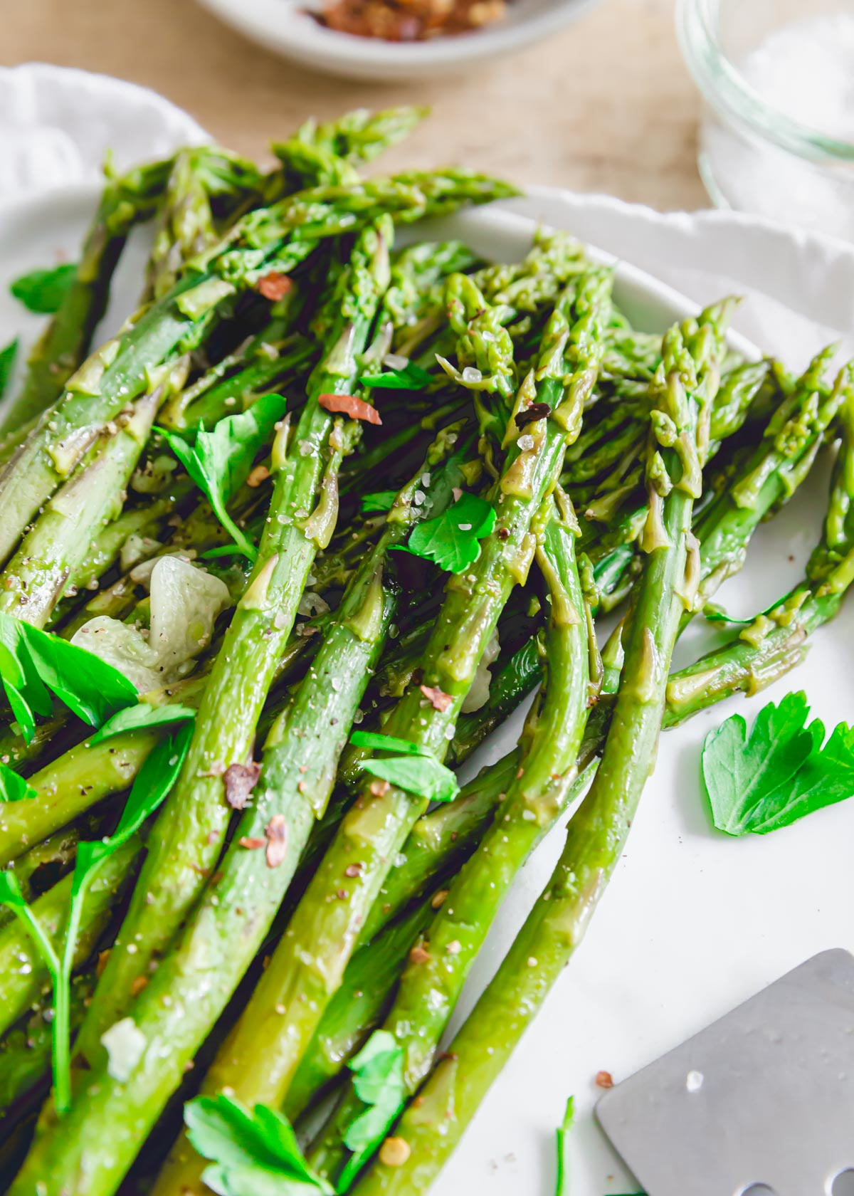 Tender cooked spring asparagus made in the Instant Pot on a plate with sea salt, parsley, garlic and chili flakes.