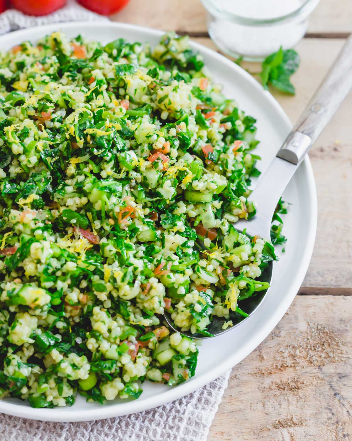 Millet tabbouleh recipe on a serving plate with a serving spoon.
