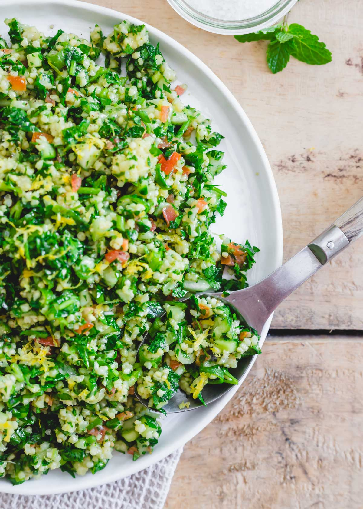 Millet tabbouleh on a white plate with a wooden serving spoon.