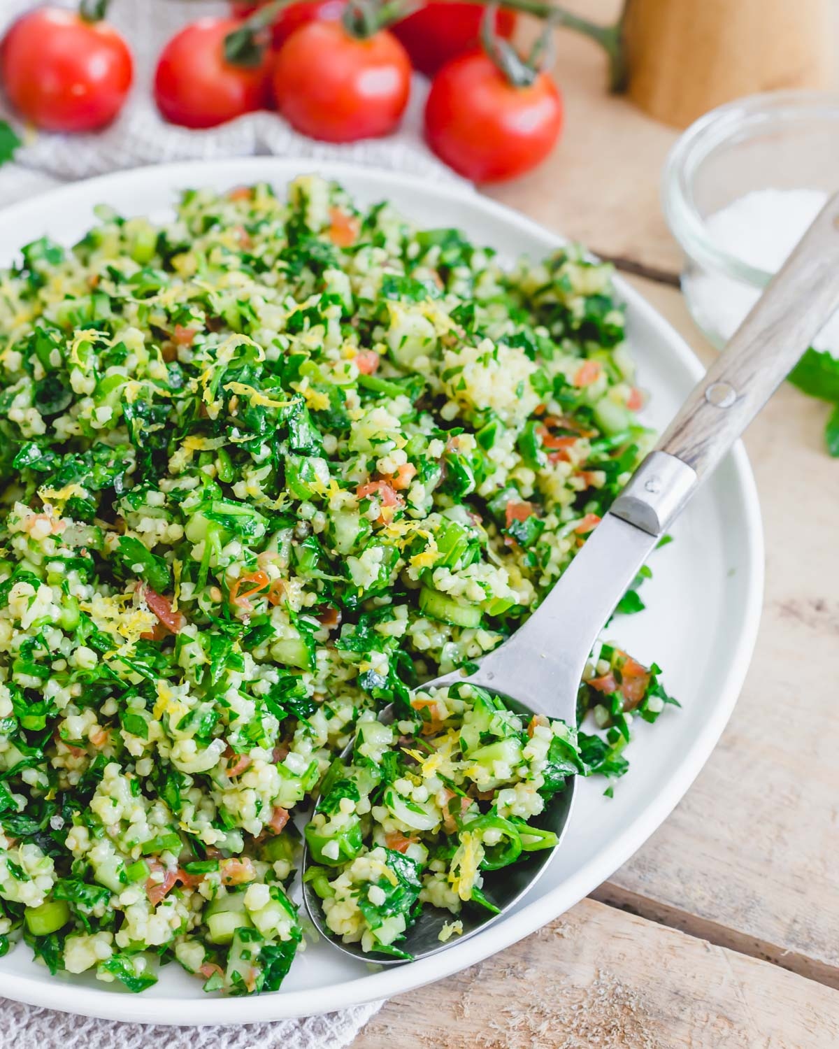 Gluten-free organic tabbouleh recipe made with millet on a plate with a serving spoon.