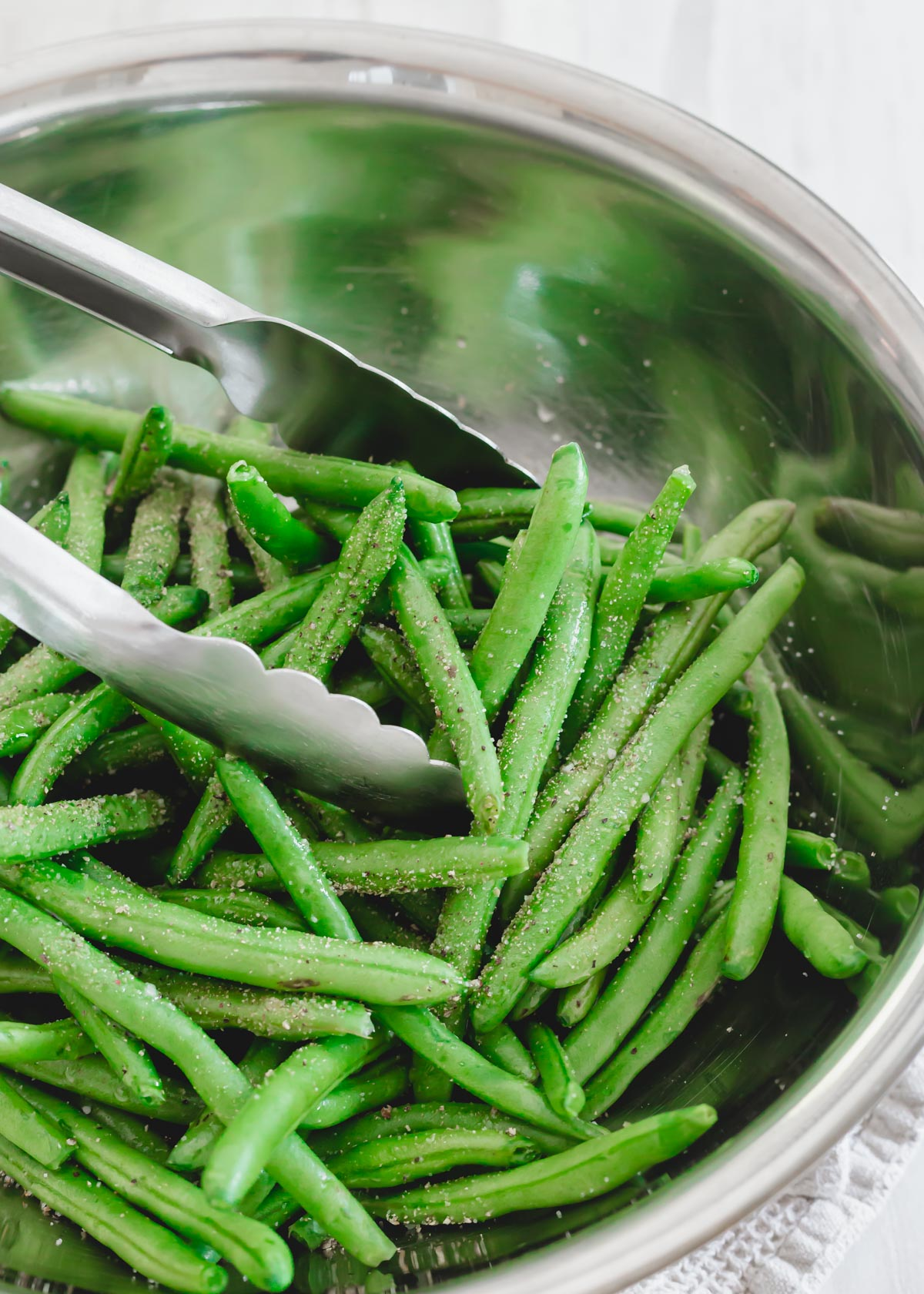 Green beans with garlic powder, salt and pepper in a metal bowl with tongs.