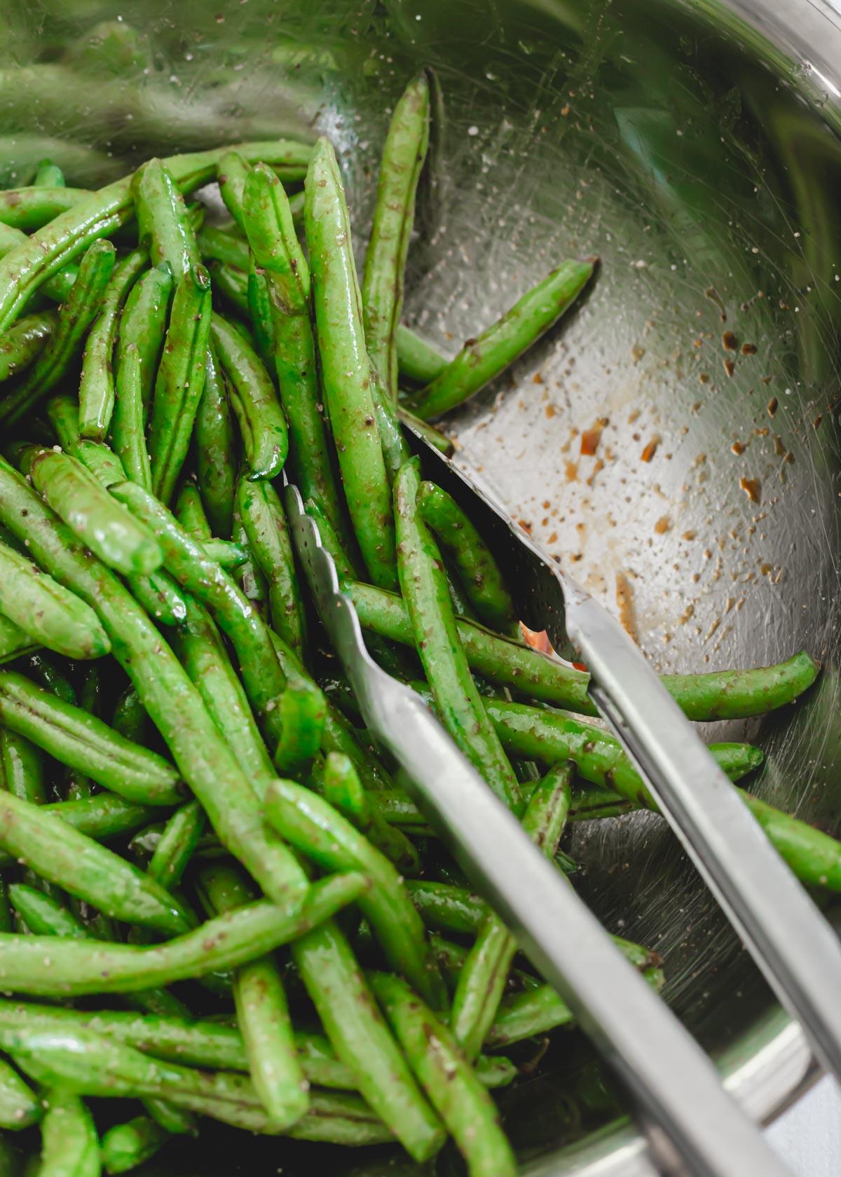 Green beans with avocado oil, tamari, garlic powder, salt and pepper in a metal bowl.