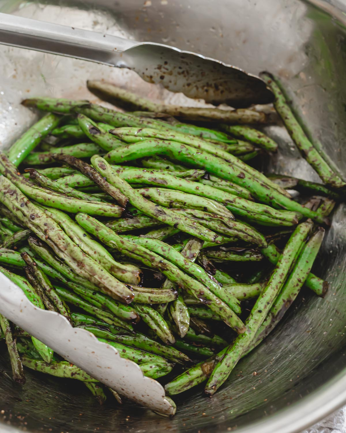 Garlic soy grilled green beans in a bowl with metal tongs.