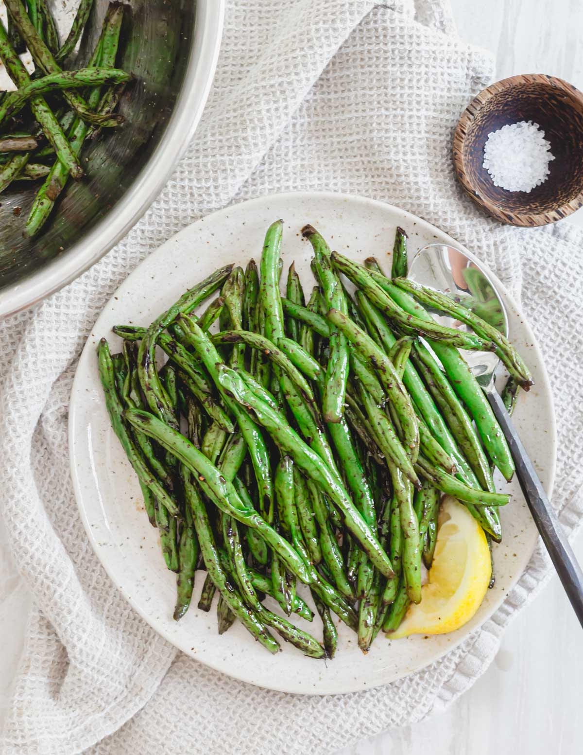 Grilled green beans with garlic and soy sauce on a plate with serving spoon, salt on the side and lemon for serving.