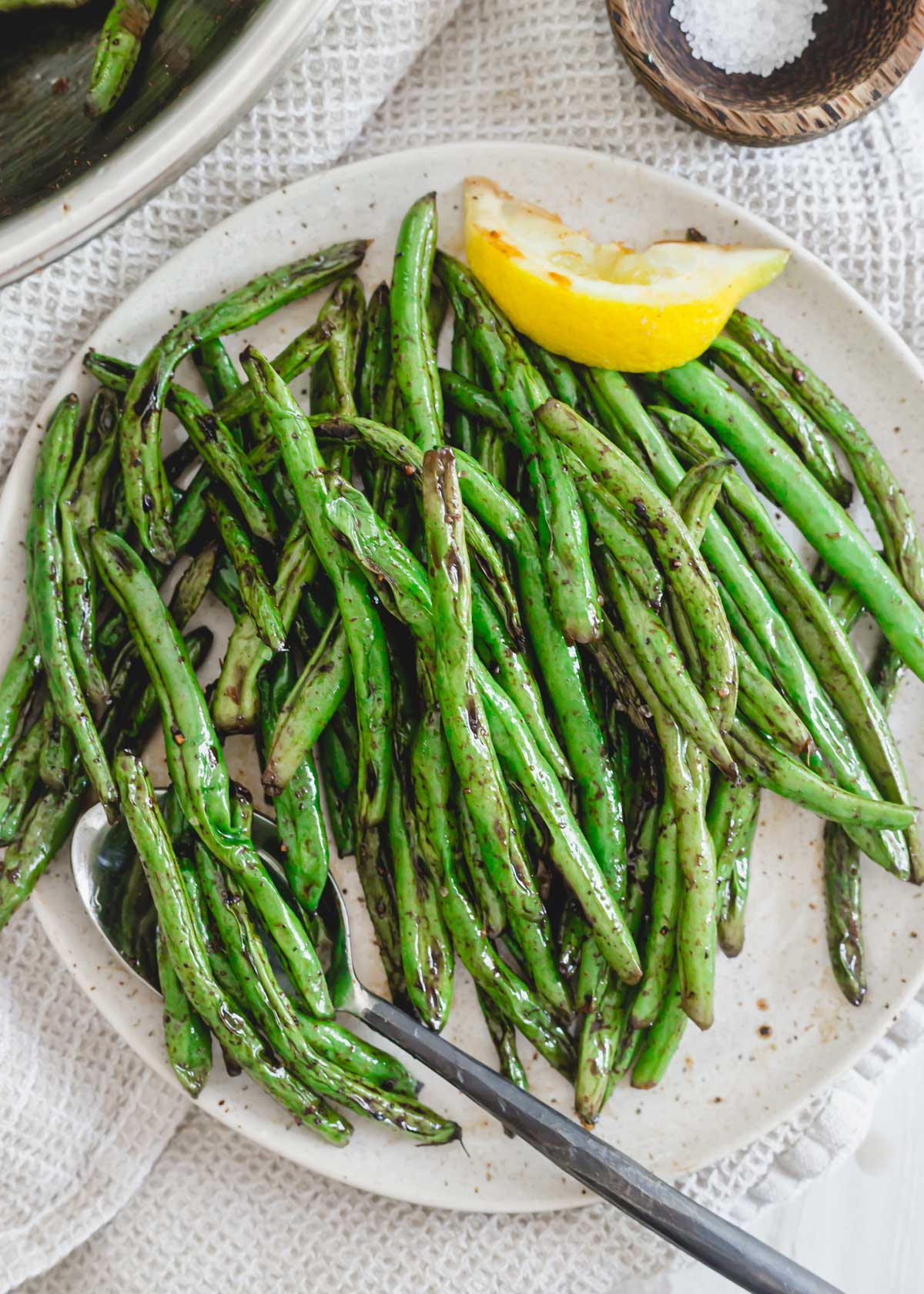Grilled green beans with lemon on a plate.