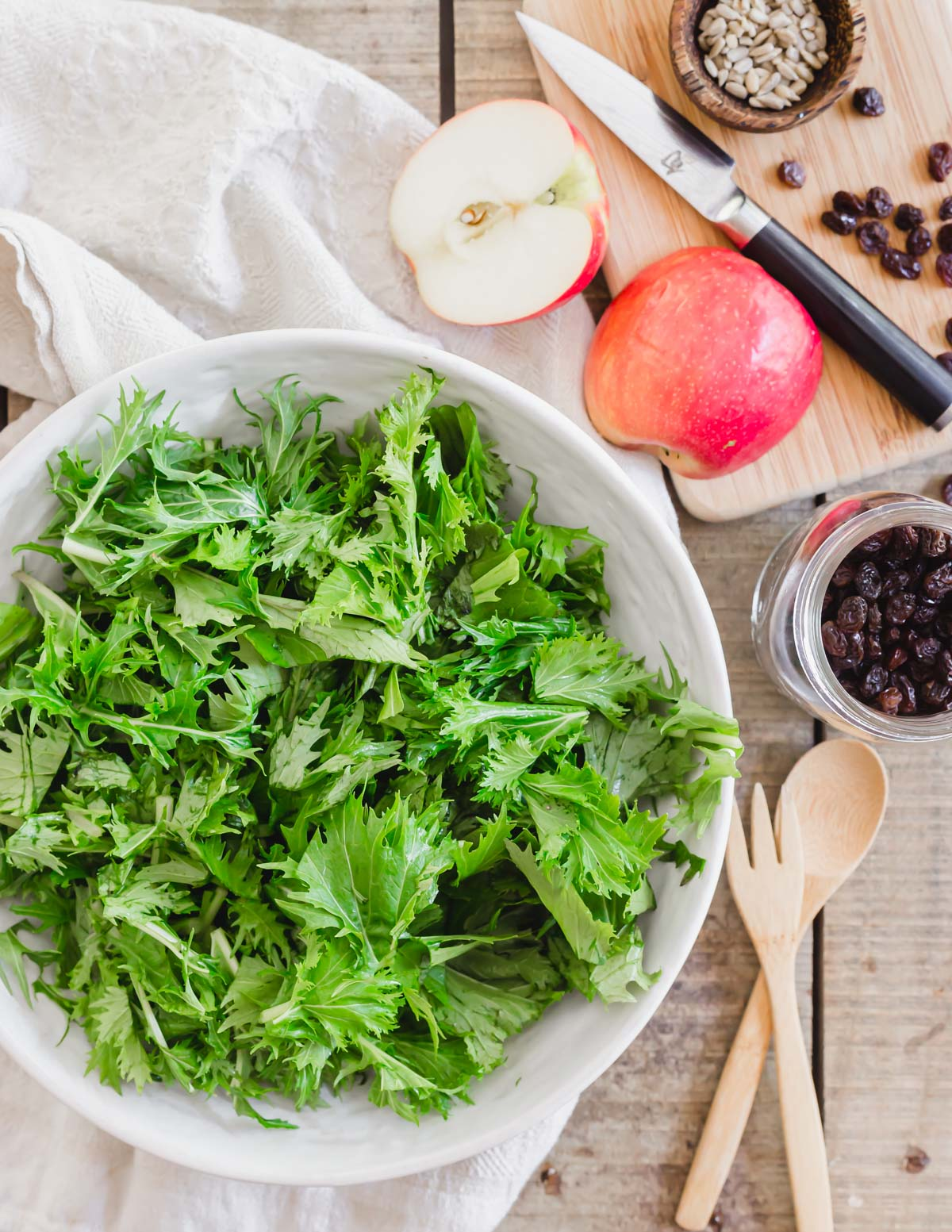 Mizuna lettuce in a bowl with salad components of raisins and an apple on the side.