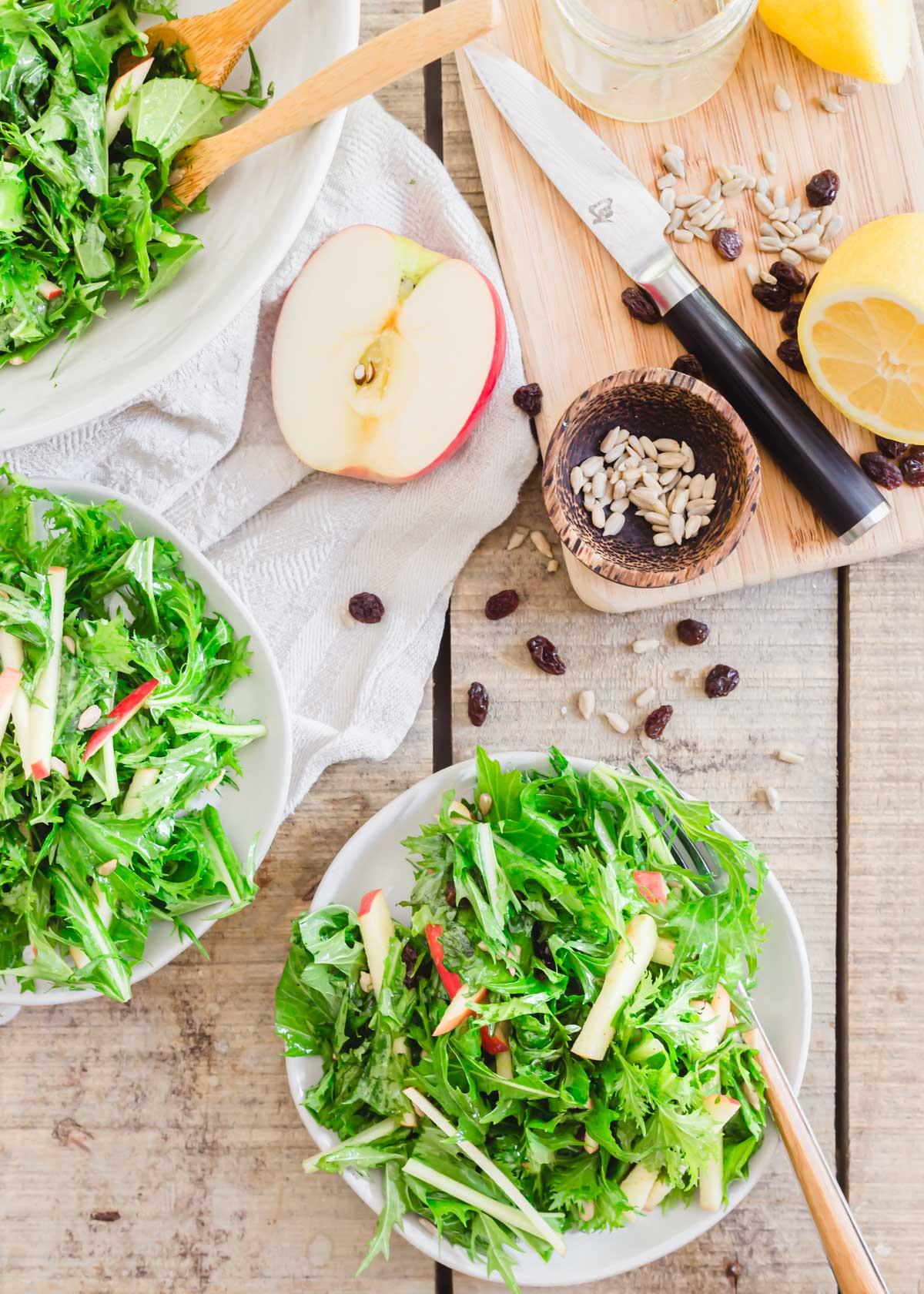 Mizuna greens salad with honey lemon dijon dressing on serving plates.