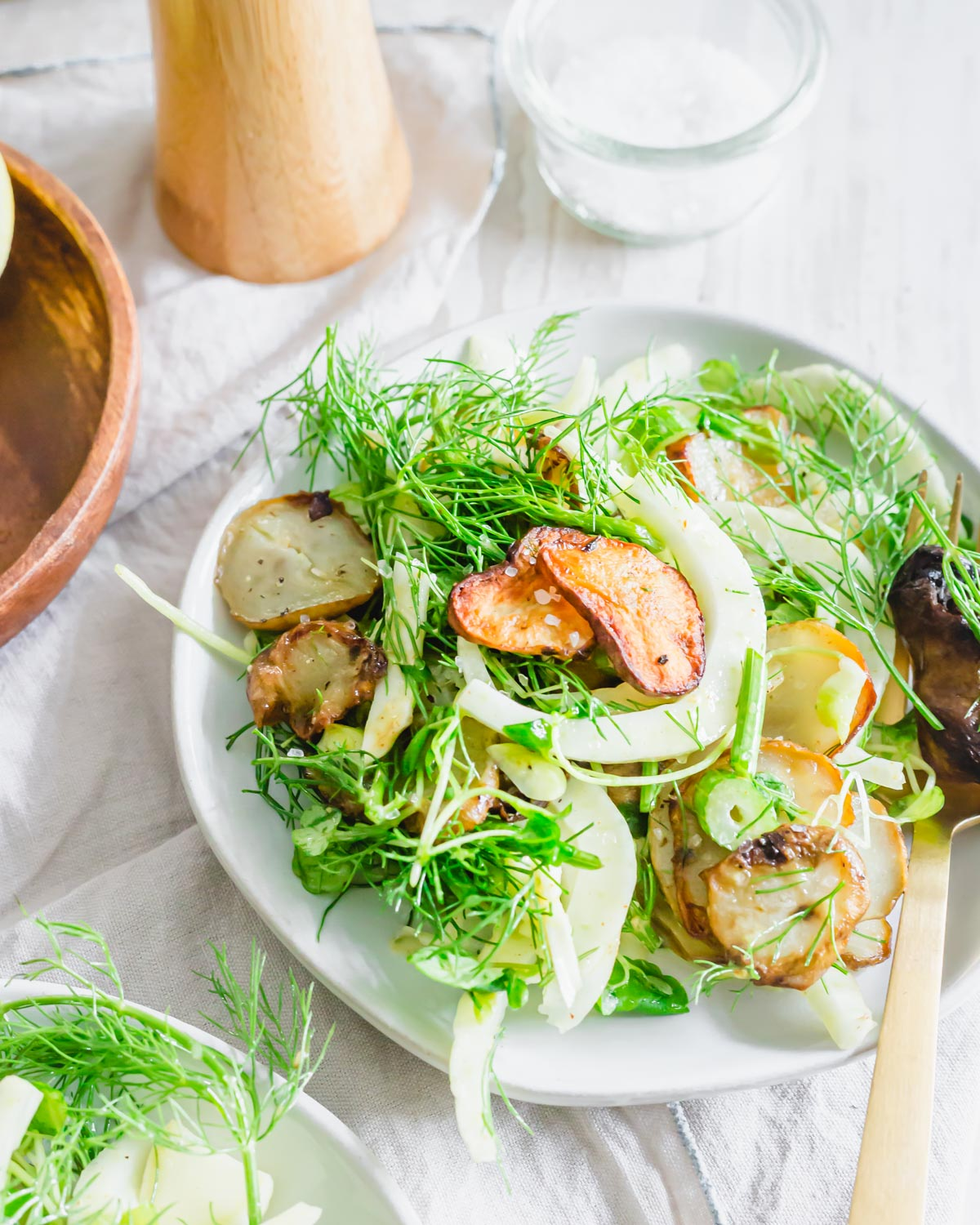 Fennel and arugula salad with roasted sunchokes tossed in a lemon mustard dressing on a plate garnished with flaky sea salt.