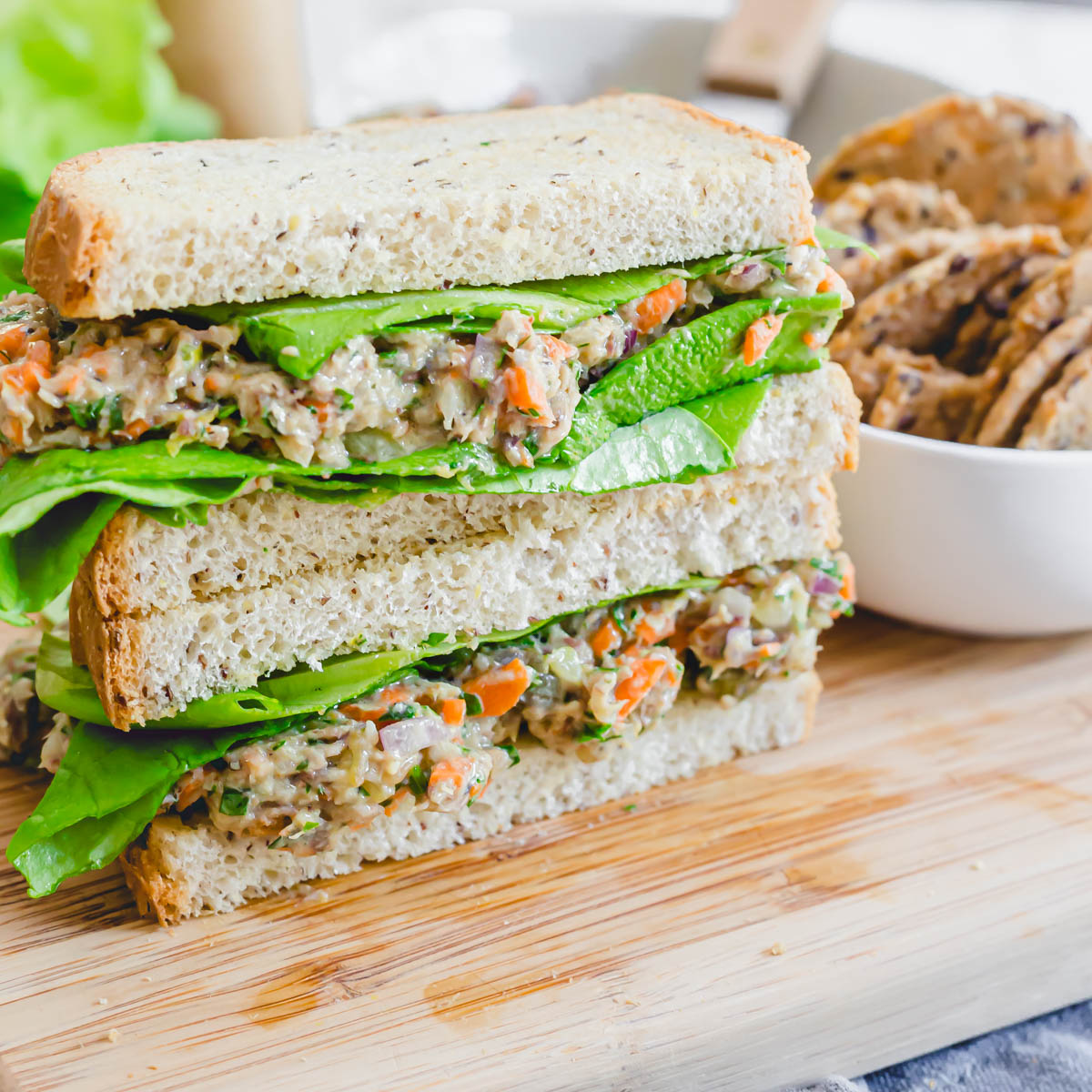 Sardine salad sandwich cut in half and stacked on top of each other on a cutting board.